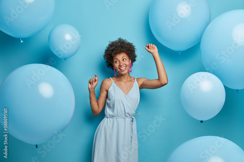 Obraz Happy dark skinned woman enjoys music at party, dances carefree, has fun and moves with rhythm of merry song, dressed in festive outfit, isolated over blue background with decorated air balloons. - fototapety do salonu