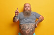 canvas print picture Shocked bearded man with fat abdomen points index finger above, shows something stunning, canot believe his eyes, stunned by big sale, has tattoed body, recommends or suggests good offer, discount