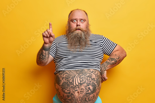canvas print motiv - Wayhome Studio : Shocked bearded man with fat abdomen points index finger above, shows something stunning, canot believe his eyes, stunned by big sale, has tattoed body, recommends or suggests good offer, discount
