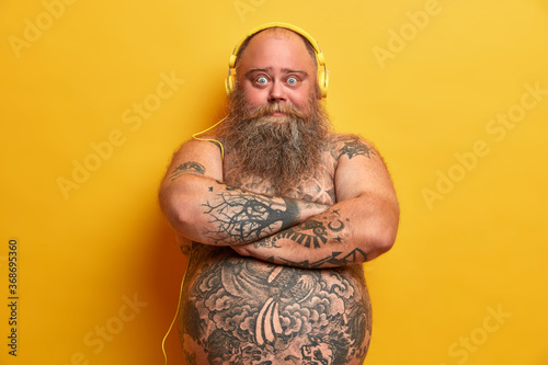 Fotografija Chubby male meloman stands with arms folded, looks confident at camera, has tatt