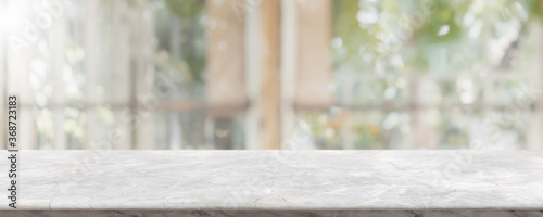 Obraz Empty white stone marble table top and blurred of interior restaurant with window view green from tree garden background background - can used for display or montage your products. - fototapety do salonu