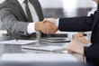 Handshake as successful negotiation ending, close-up. Unknown business people shaking hands after contract signing in modern office
