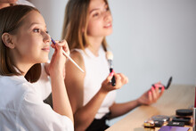 Attractive Young Caucasian Girls Applying Cosmetics On Face, Doing Make-up On Themselves During Master Class Of Professional Visagiste