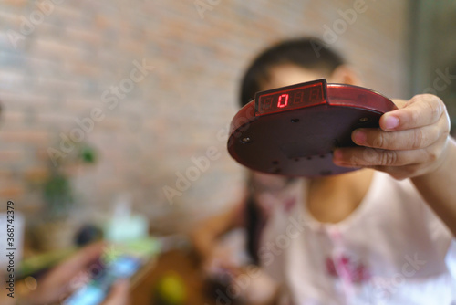 Photo Kid hand holding restaurant queue wireless pager