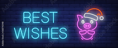 Best wishes neon sign. Glowing inscription with cute pink piglet in red santa cap on brick wall background. illustration can be used for New Year, greeting, celebration