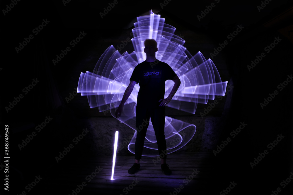 Fotografie, Obraz Silhouette of a man standing with a lightsaber with neon drawings and leds at lightpainting