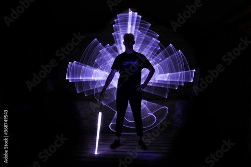 Photo Silhouette of a man standing with a lightsaber with neon drawings and leds at lightpainting