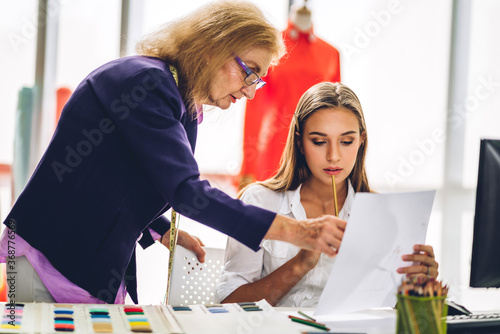 Portrait of woman fashion designer stylish sitting and working with color samples.Attractive woman working with mannequins standing and colorful fabrics at fashion studio