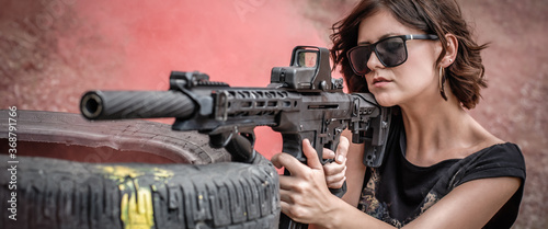 Obraz na plátně Beautiful and attractive woman soldier shooting with rifle machine gun from behind and around cover or barricade