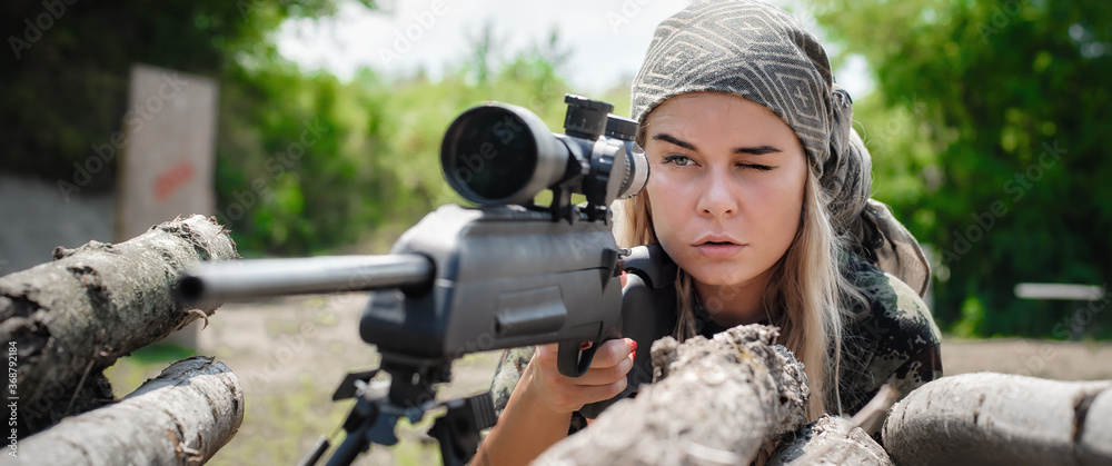 Fototapeta Female soldier shooting with sniper rifle. Woman with weapon. Firearm army shooting and tactical training. Outdoor shooting range