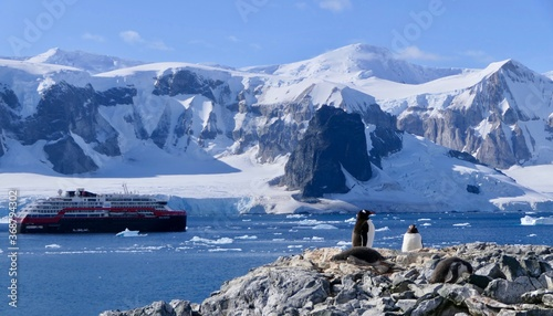 Penguin colony with expedition ship before mountains and glacier, Antarctica Fototapeta