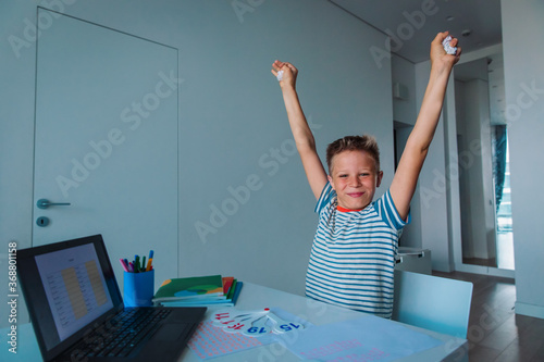 Obraz kid enjoy learning online, happy boy passed exam remotely - fototapety do salonu
