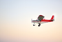 Small Ultralight Airplane With Overhead Wing And Single Propeller Flying In Sky. Such Aircraft Are Used For Recreational, Sport And Flight Training.