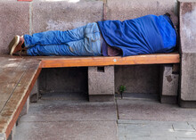 Homeless Man Sleeping Rough On A Wooden Park Bench During The Day. A Symbol Of The Growing Problems Of Homelessness And Poverty Especially In The Cities