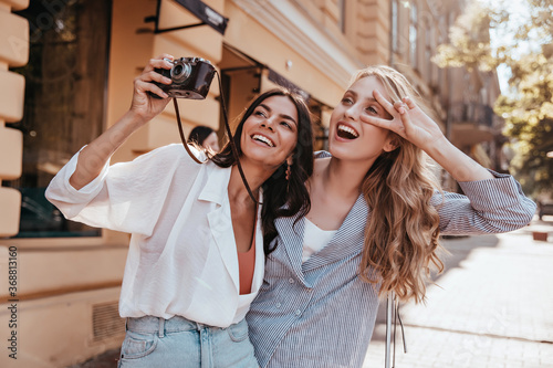 Fototapeta Long-haired woman in striped jacket enjoying weekend with friend