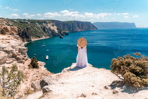 Fototapeta From behind, a woman is seen in a white flying dress fluttering in the wind. In a straw hat, walking down the stairs against the background of the sea with rocks and boats. The concept of travel obraz na płótnie
