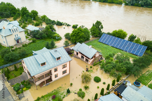 Canvastavla Aerial view of flooded house with dirty water all around it.