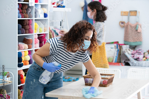 Foto Shop assistant female wearing a hygienic face mask and doing deep cleaning on a small retail store
