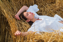 Sensual Woman Lying In The Hay. Girl In White Shirt And Lies On A Haystack. Female Portrait In Field In Countryside.