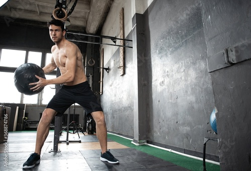 Obraz Young strong sweaty focused fit muscular man doing throwing medicine ball up on the wall for crossfit training hard core workout in the gym - fototapety do salonu