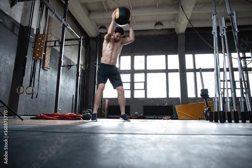Obraz Fit man throwing medicine ball doing ball slam against gym floor or shoulder press upper body workout exercise. Cross training at fitness center. - fototapety do salonu