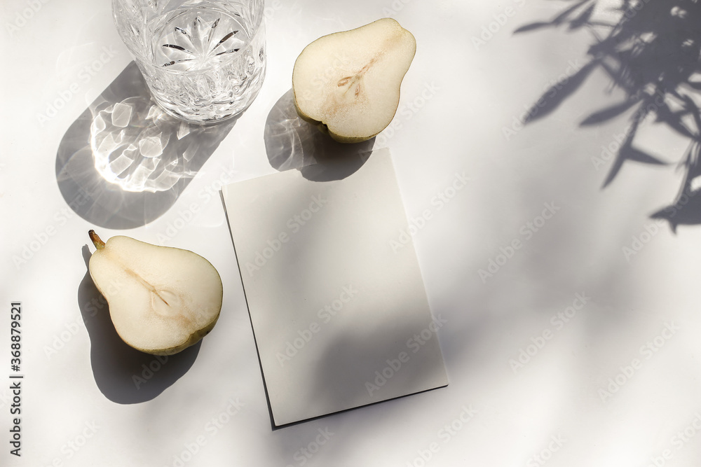 Fototapeta Summer stationery still life scene. Glass of water and cut pear fruit in sunlight. White table. Blank paper card, invitation mockup scene, olive branches shadows. Flat lay, top view, no people.