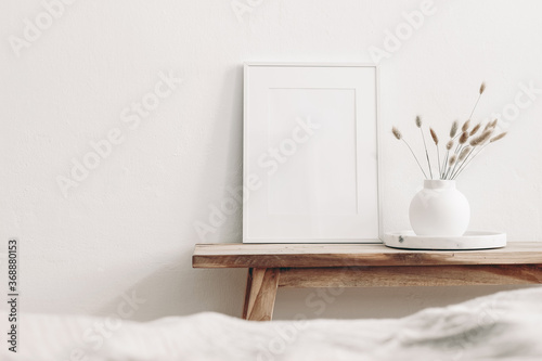 Obraz Portrait white frame mockup on vintage wooden bench, table. Modern white ceramic vase with dry Lagurus ovatus grass and marble tray. Blurred beige linen blanket in front. Scandinavian interior. - fototapety do salonu