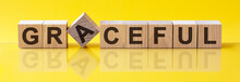 Word GRACEFUL Is Made Of Wooden Building Blocks Lying On The Table And On A Light Yellow Background. Concept