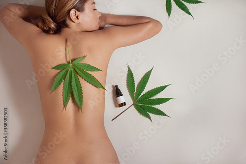 Fototapeta Naked woman's body with CBD liquid oil made from cannabis extract for a natural skin treatment. Woman with cannabis leaf. Cosmetology and Spa concept. Isolated on gray background obraz