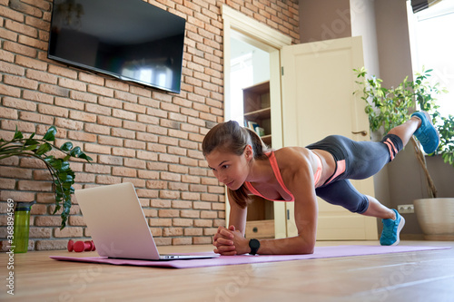 Fotografia, Obraz Fit sporty young woman doing plank online workout exercise at home