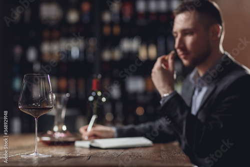 Photo Professional sommelier examining smell of wine cork and making notes aroma degus