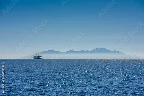 Obraz ferry ship in front of a greece island in the mist - fototapety do salonu