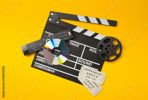 Single, black, open movie clapper or clapper-board with dvd movie disc, film reel, remote control and movie theatre tickets on yellow or orange - digital movie, home cinema or movie night concept