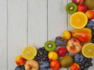 Fruit frame located on the right on a white plank background. Close up. Good nutrition. Space for text.