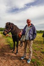 Helgenaes, Denmark  A Man Stads With A Horse Ready For Horsebackriding