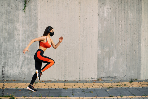 Obraz Woman running wearing mask for protection - fototapety do salonu