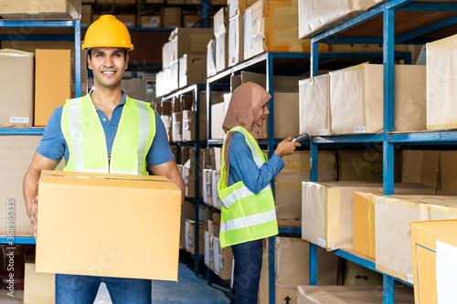 Obraz Indian warehouse worker hold cardboard box - fototapety do salonu