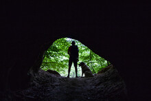 Man And Dog Silhouette At The Entrance Of A Cave