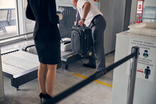 Female Traveler Passing Through Luggage Control In Airport