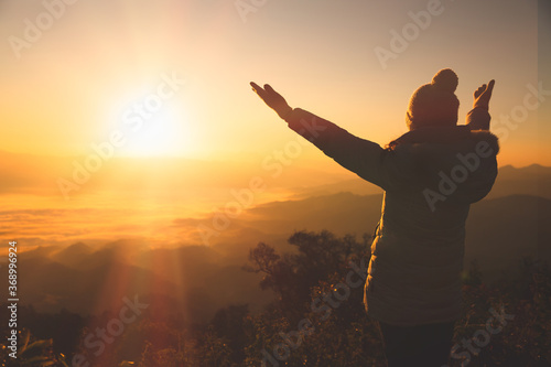 фотография Copy space of silhouette woman raise hand up on top of mountain and sunset  background