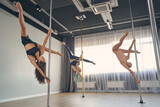 Group of beautiful young women performing pole dance tricks