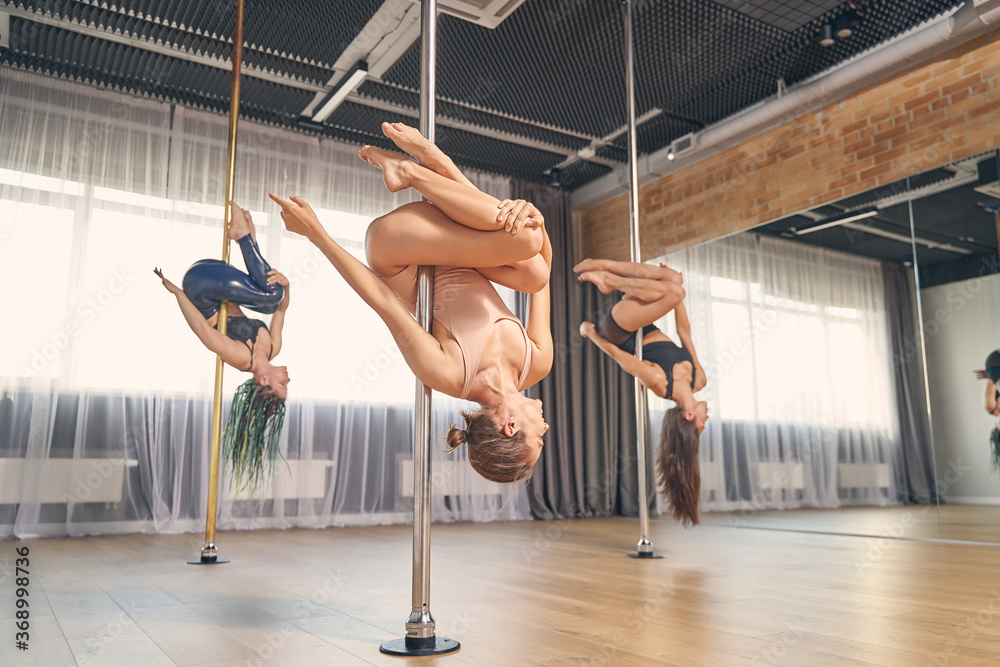 Fototapeta Group of charming female dancers performing pole dance tricks