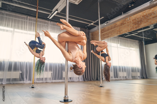 Obraz Group of charming female dancers performing pole dance tricks - fototapety do salonu