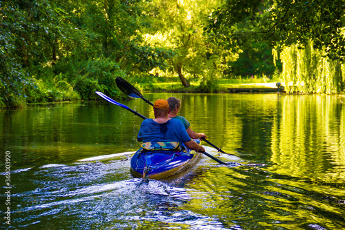 Two people in a blue kayak row on the river in the Spreewald.
