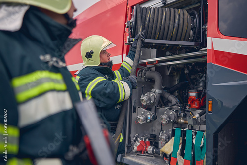 Canvas-taulu Fireman wearing safe helmet standing next to the fire engine