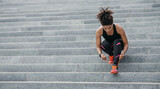 Fototapeta Na drzwi - Muscular african american woman in sportswear, with modern headphones, fitness tracker, tying laces on sneakers on stairs