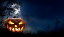 A Spooky Halloween Pumpkin, Jack O Lantern, With An Evil Face And Eyes On The Grass In A Graveyard With A Misty Night Sky Background With A Full Moon.