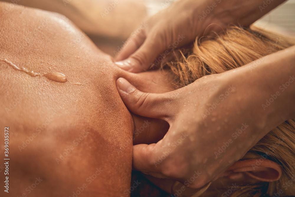 Fototapeta Professional therapist doing neck massage to woman in beauty salon