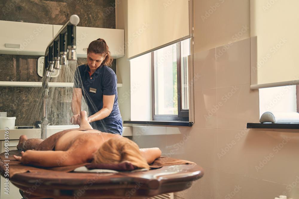 Fototapeta Customer lying on the brown desk in spa center under shower rain