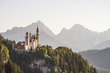 "The Fairytale Castle ""Neuschwanstein"" In Bavaria During Sunset With Mountains In The Background"
